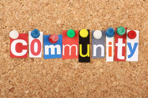 "The word ""community"" pinned to a bulletin board, each letter is a different color and pinned with a different color thumb tack."