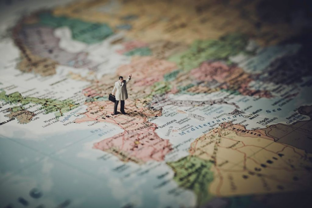 Picture of a Map of the world with a figurine of a man standing on it, located in Europe