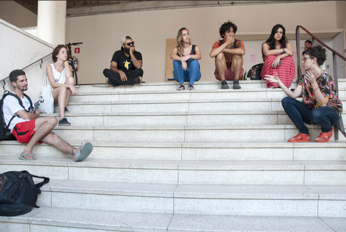 College students sitting on the steps of a campus